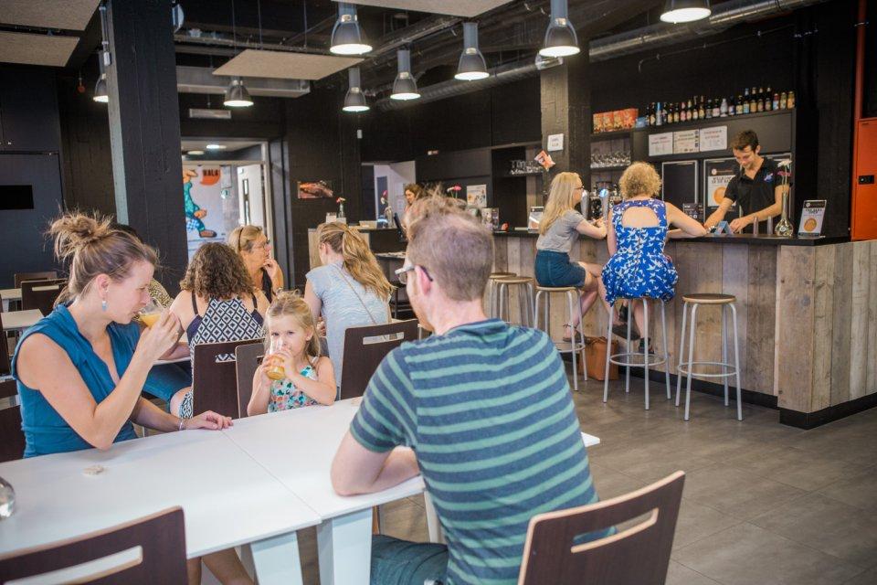Familie met kindje drinken een glaasje in de hostel bar