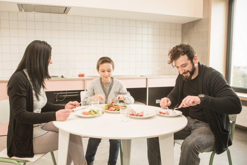 Famille en train de manger dans la cuisine commune