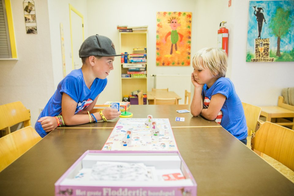 Twee kinderen spelen een spel in de gemeenschappelijke zithoek
