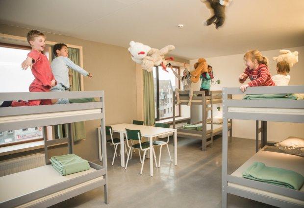 Kinderen gooien pluchen beren in de kamer
