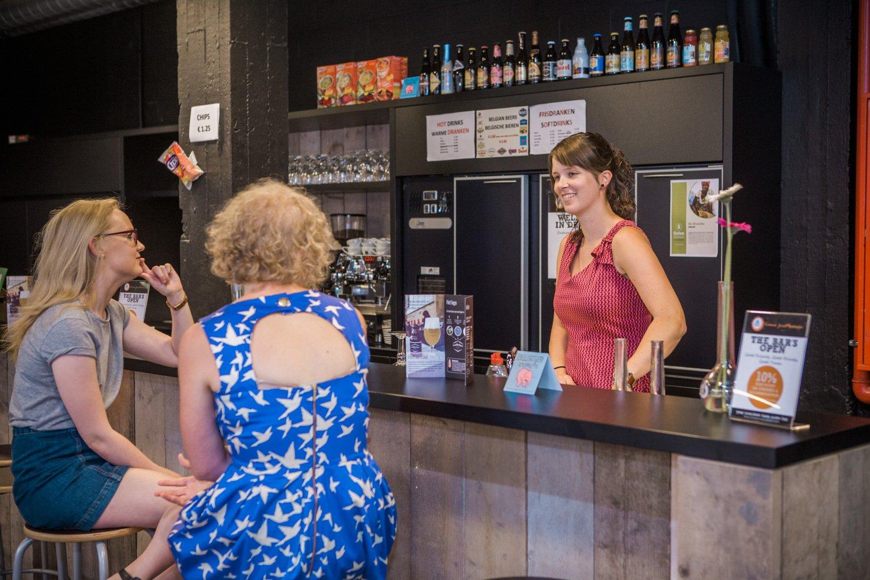 Twee gasten maken een praatje met de hostel manager in de bar