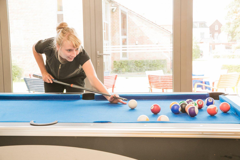 jonge vrouw speelt een spelletje biljart